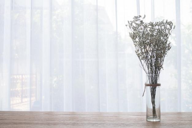 Tabela de madeira com a flor secada do gypsophila no contexto branco da cortina.