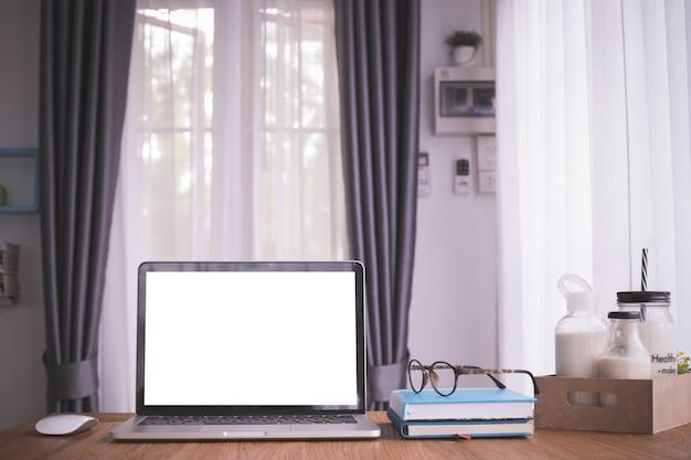 Tabela de madeira com a tela vazia no portátil, no papel do caderno e no leite na caixa da caixa na sala de visitas.