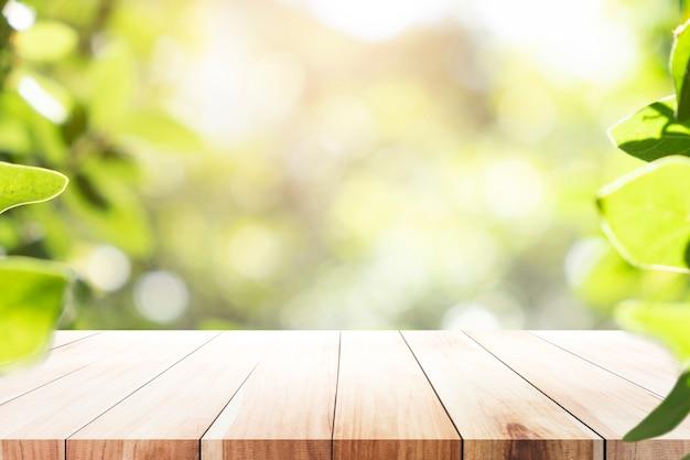 Tabela de madeira com fundo do borrão do bokeh verde.