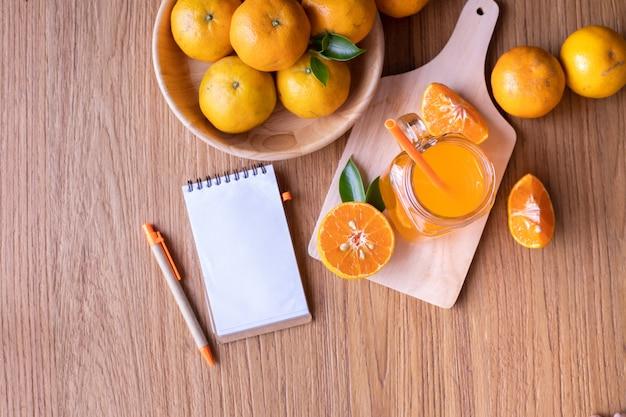 Tabela de madeira com o copo do suco de laranja frio e a tela vazia no papel do bloco de notas na tabela de madeira.