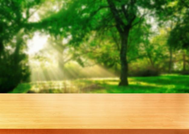 Tabela de madeira de brown no fundo verde da natureza do borrão.