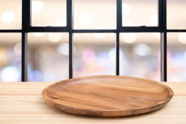 Tabela de madeira de perspectiva e bandeja de madeira na parte superior sobre fundo de loja de café de desfoque
