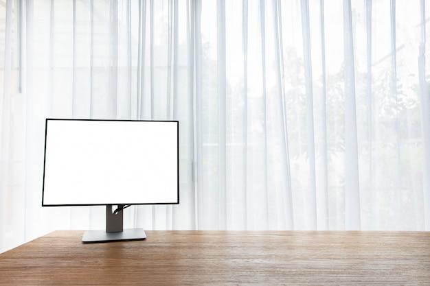 Tabela de madeira do escritório com a tela vazia no monitor na janela da cortina em casa.