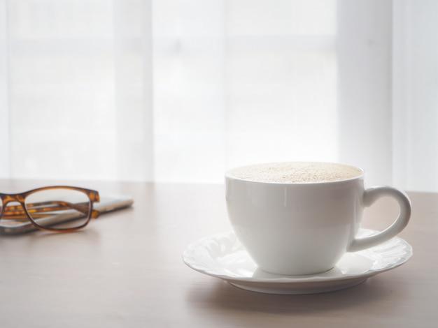 Tabela de madeira do escritório com o copo de café branco do café do latte.