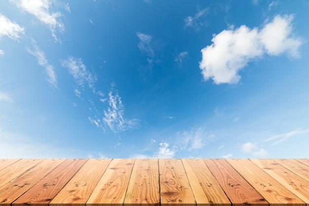 Tabela de madeira no céu azul e no fundo branco da nuvem.