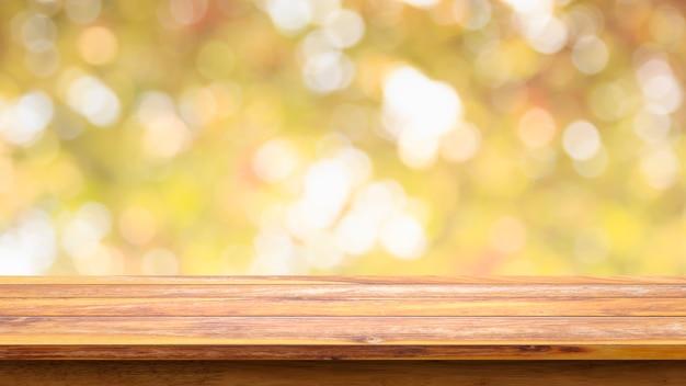 Tabela de madeira vazia com fundo amarelo abstrato do bokeh.