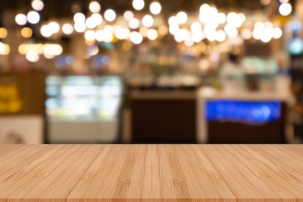 Tabela de madeira vazia da perspectiva na parte superior sobre o fundo do borrão.