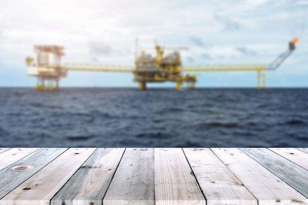 Tabela de madeira vazia da prancha com plataforma de petróleo e gás ou equipamento offshore de plataforma de construção desfocar o fundo.