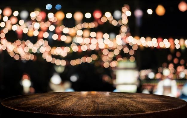 Tabela de madeira vazia seletiva na frente do fundo claro festivo borrado abstrato com pontos claros e bokeh