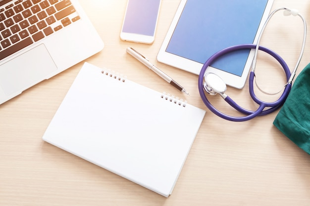 Tabela de médico com acessórios médicos e caderno em branco.