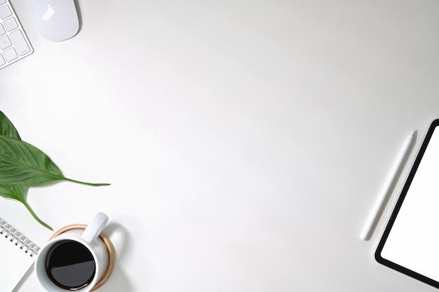 Tabela de mesa branca de escritório com computador, suprimentos, tablet e caneca de café.
