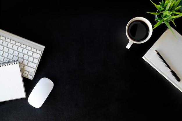 Tabela de mesa de couro do escritório com computador portátil, fontes, copo de café e flor.