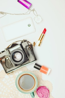 Tabela de mesa de escritório branco com smartphone, câmera vintage, café e cosméticos.
