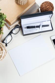 Tabela de mesa de escritório branco com um monte de coisas sobre ele. vista do topo