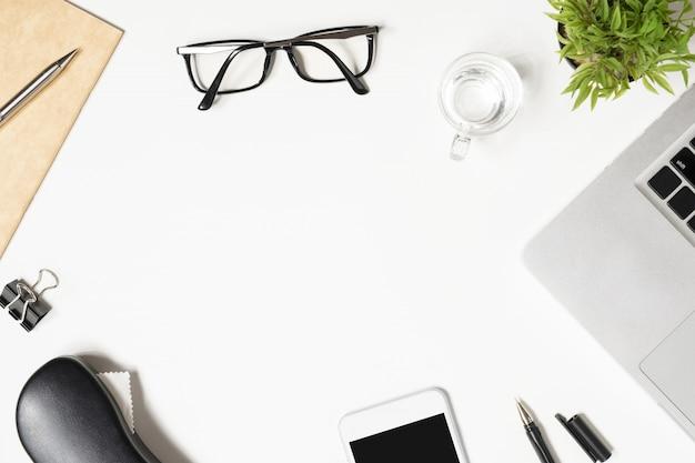 Tabela de mesa de escritório branco com um monte de coisas sobre ele.