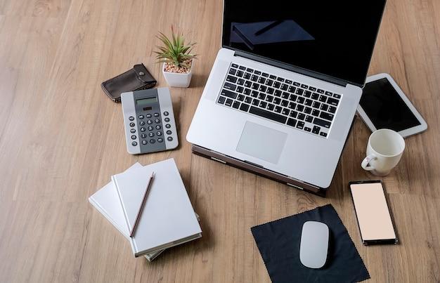 Tabela de mesa de escritório de madeira com laptop e suprimentos.
