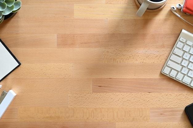 Tabela de trabalho de madeira com espaço do portátil, do café e da cópia.
