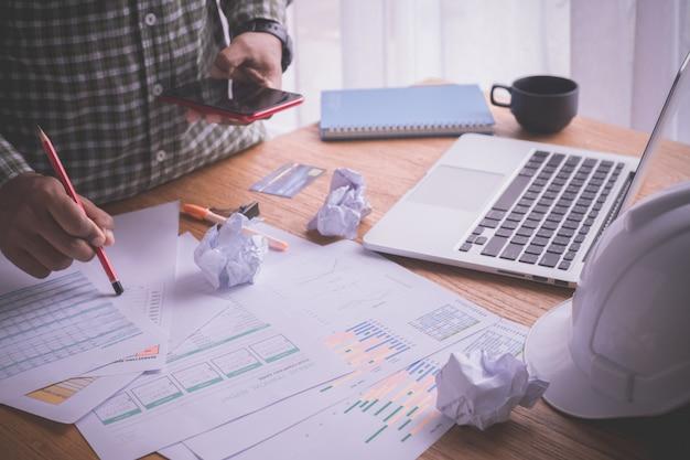 Tabela do escritório com o homem de negócios ocupado que usa o telefone, mesa ocupada no escritório domiciliário.