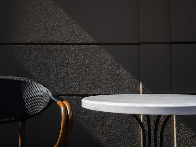 Tabela e cadeira contra parede cinza no café. luz solar atinge uma mesa de café vazia