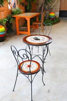 Tabela e cadeira da mobília de jardim no balcão da cafetaria.