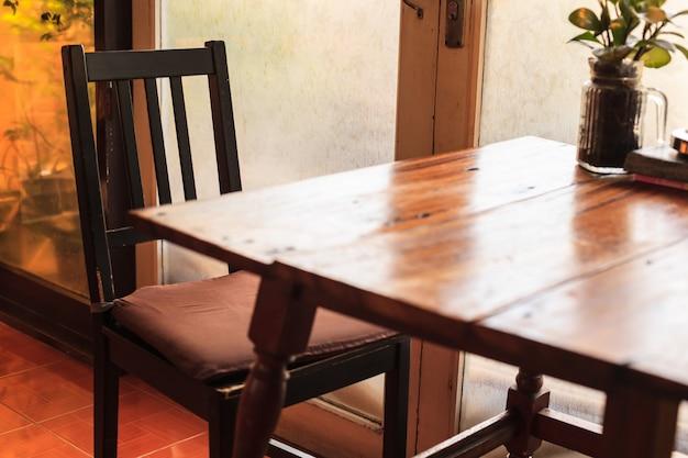 Tabela e cadeiras de madeira rústicas com ajuste morno da luz natural iluminado através da janela de vidro da porta.