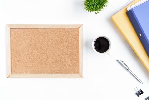Tabela e equipamento brancos da mesa de escritório para trabalhar com café preto e placa vazia na vista superior e no conceito liso do raio.