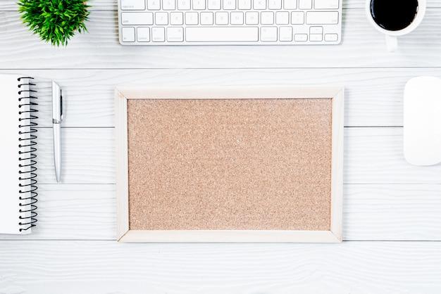 Tabela e equipamento de madeira brancos da mesa de escritório para trabalhar com café e placa vazia na vista superior e no conceito liso do raio.