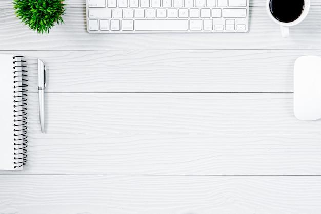 Tabela e equipamento de madeira brancos da mesa de escritório para trabalhar com café na vista superior e no conceito liso do raio.