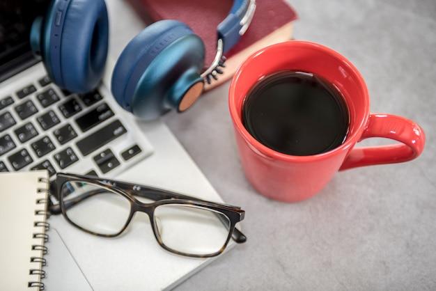 Tabela moderna da mesa de escritório com portátil, smartphone e outras fontes com xícara de café.