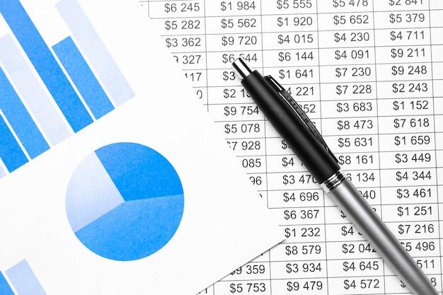 Tabelas de negócios, gráficos e uma caneta
