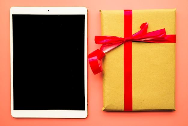 Tablet com caixa de presente na mesa