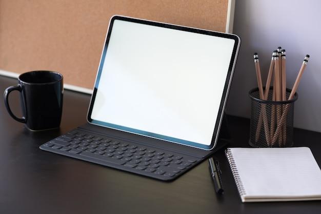 Tablet com caixa de teclado inteligente com tela em branco na mesa de madeira escura