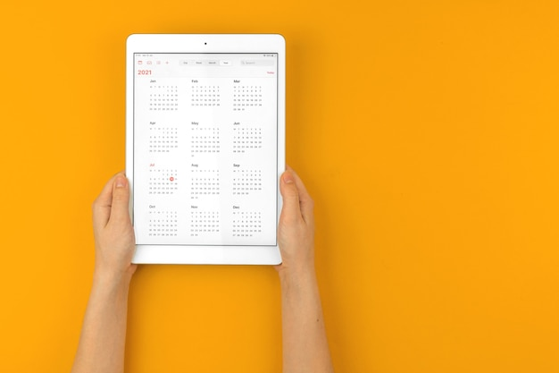 Tablet com calendário aberto 2021, mão de mulher segura o tablet em uma área de trabalho amarela brilhante com espaço de cópia