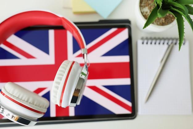 Tablet com imagem da bandeira britânica com fones de ouvido e caderno com caneta deitada na mesa
