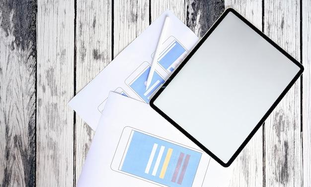 Tablet com layout de smartphone de tela e protótipo em branco na mesa de madeira.