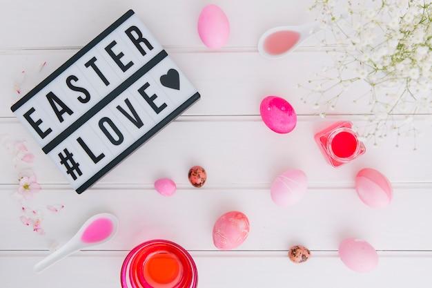Tablet com o título de amor de páscoa perto de ovos entre galho de flor e latas com líquido de tintura