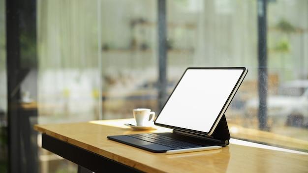 Tablet com teclado em tela vazia e espaço de cópia para exposição do produto na mesa de madeira