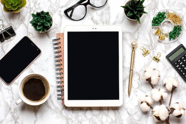 Tablet com tela preta, óculos, xícara de café, caneta, smartphone, suculentas no tampo da mesa de mármore