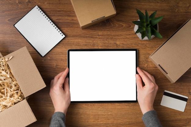 Tablet com tela vazia cercada por pacotes