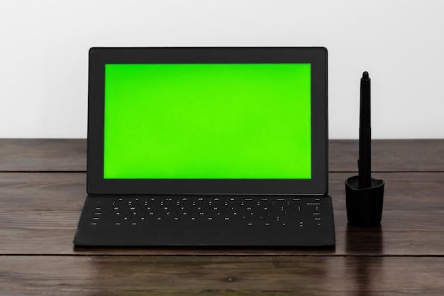 Tablet com tela verde e caneta de assinatura eletrônica para tablet em uma mesa de madeira.