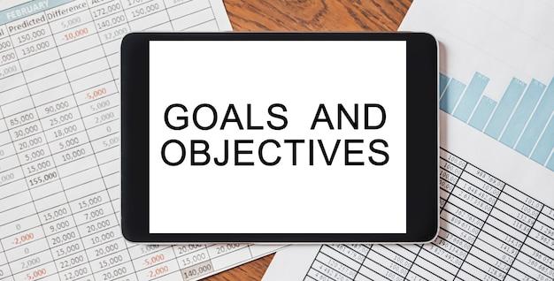 Tablet com texto de metas e objetivos em sua área de trabalho com documentos, relatórios e gráficos
