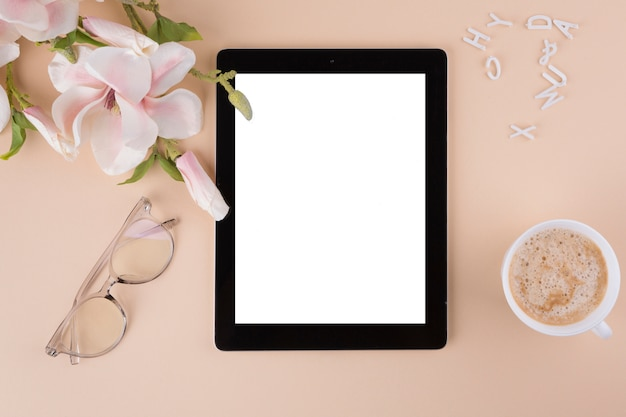 Tablet com xícara de café e flores