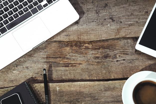 Tablet, computador, smartphone, bloco de notas e caneta em cima da mesa com uma xícara de café