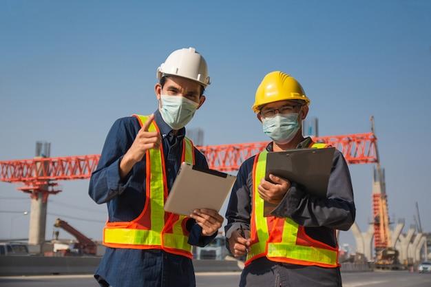 Tablet de dois engenheiros trabalhando na construção de uma estrada local, construtor de arquitetura de homem asiático, topógrafo profissional