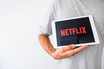Tablet de exploração do homem anônimo com o logotipo da Netflix
