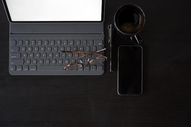 Tablet de itens de negócios, caneta, celular na mesa de madeira escura espaço de trabalho e cópia espaço