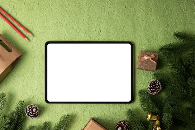 Tablet de maquete de tela em branco no natal verde.