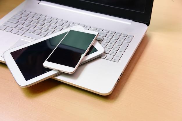 Tablet de notebook computador portátil e telefone inteligente em fundo de madeira