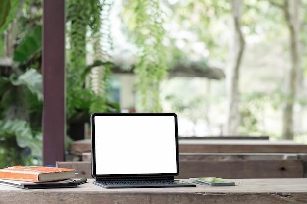 Tablet de tela branca em branco de maquete com teclado mágico na mesa de madeira com fundo de natureza.