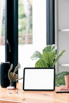 Tablet de tela branca em branco de maquete e gadget na mesa de madeira na sala de estar, visão vertical.